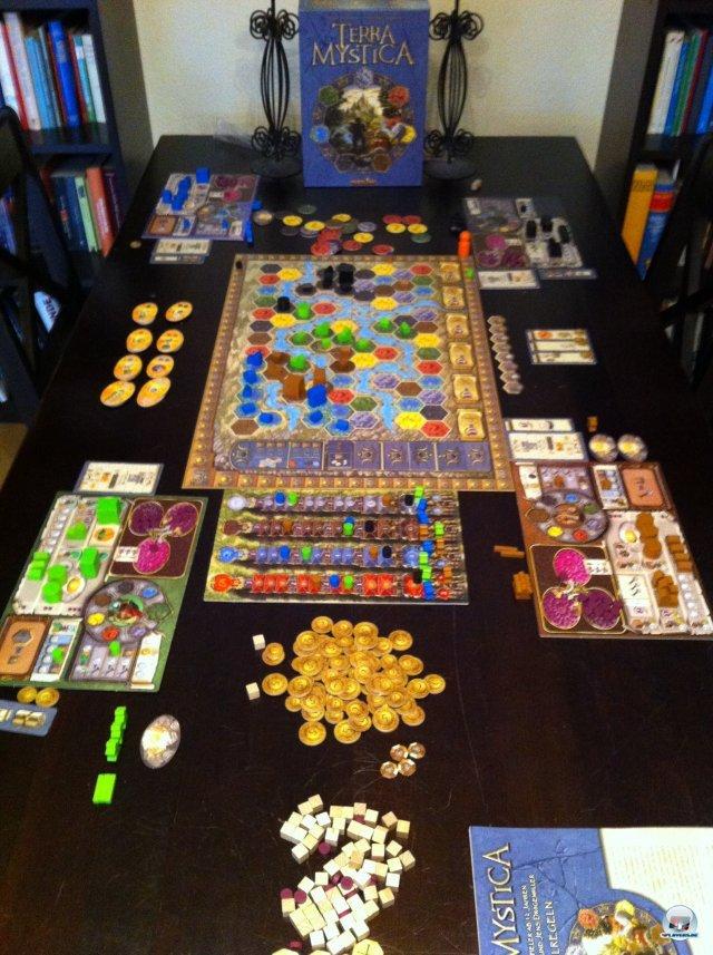 Das Spielmaterial ist hochwertig und edel illustriert. Zu viert braucht man Platz für die Weltkarte, die Spielertableaus und all die Plättchen und Steine.
